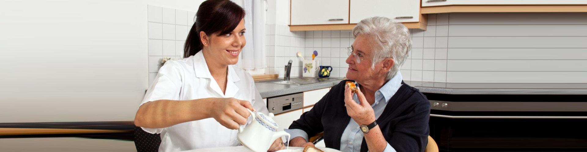 a caregiver serving food to senior